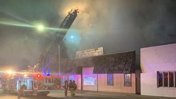 The Hutchinson Fire Department's Quint truck pours water on the roof of a commercial building on East Fourth Avenue discovered burning early Sunday morning. The building, heavily involved in fire when firefighters arrived, was destroyed.