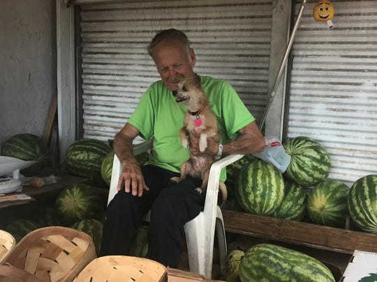 Former Alice Manufacturing employee Charles Watkins at his roadside produce stand with his dog, Elvis.