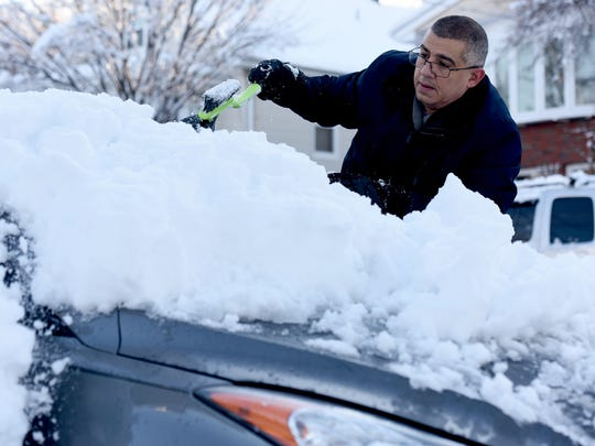 Luis Arroyo prepares for work by clearing the snow off his car on Summer St. in Clifton on Thursday, March 8, 2018.