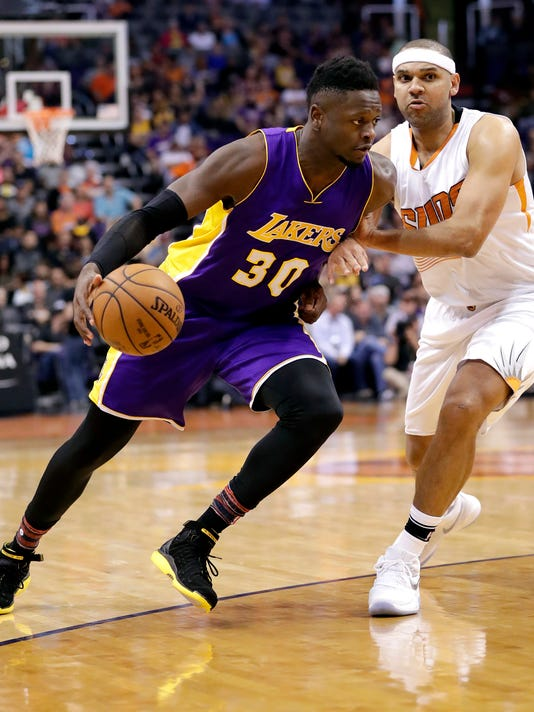 Los Angeles Lakers forward Julius Randle (30) drives past Phoenix Suns forward Jared Dudley during the first half of an NBA basketball game, Wednesday, Feb. 15, 2017, in Phoenix. (AP Photo/Matt York)