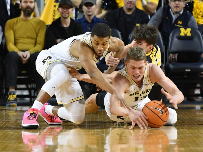 Michigan's Jaaron Simmons and Moritz Wagner fight for