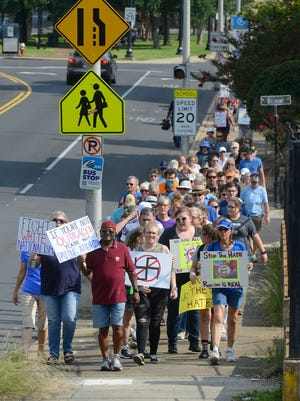 Ralliers make their way up Palafox St. Sunday, August 13, 2017 during the Love is Louder-Stand with Charlottesville walk to support peace in Charlottesville. More than 100 people made their way up Palafox in silence carrying signs to stop racism and promote peace.