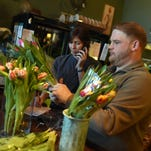Blooms employee Stephanie Casey organizes flowers as the store prepares for Valentine's Day orders during the week.