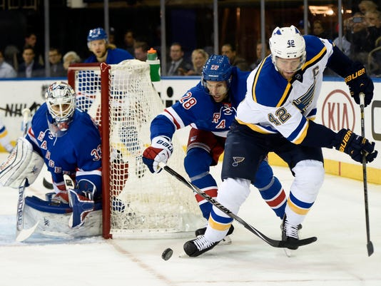 New York Rangers center Dominic Moore (28) battles for the puck with St. Louis Blues center David Backes (42) as New York Rangers goalie Cam Talbot (33) defends the net in the first period of an NHL hockey game at Madison Square Garden on Monday, Nov. 3, 2014, in New York. (AP Photo/Kathy Kmonicek)