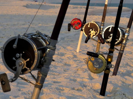 Rods and reels are prepared for a night of shark fishing in the Gulf of Mexico by Earnie Polk and the group of friends and family members he fishes with.
