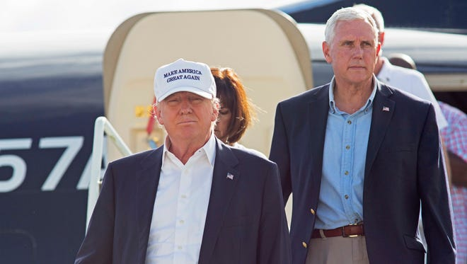 Republican presidential candidate Donald Trump, followed by his running mate, Indiana Gov. Mike Pence, emerges from his plane as he arrives to tour the flood damaged city of Baton Rouge, La., Friday, Aug. 19, 2016.