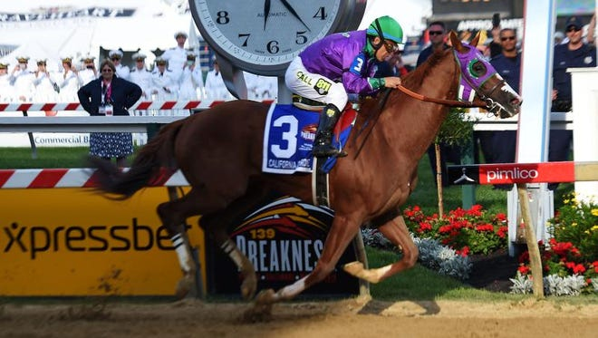 California Chrome, ridden by Victor Espinoza, crosses the finish line to win the 139th running of the Preakness Stakes at Pimlico Race Course on Saturday in Baltimore, Maryland.