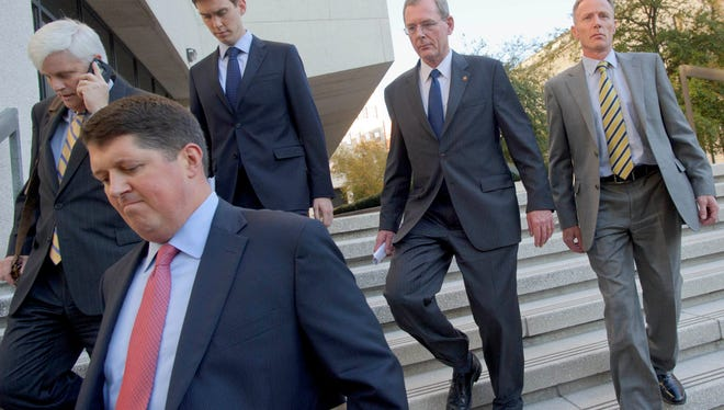 FILE  - In this Nov. 28, 2012 file photo, David Rainey, second right, a former BP vice president during the Deepwater Horizon oil rig explosion, leaves Federal Court after being arraigned on obstruction of a federal investigation in New Orleans. On Friday, June 5, 2015, Rainey was found not guilty of making false statements to investigators in connection with the 2010 Gulf of Mexico oil spill. Prosecutors said Rainey, in the early days of the spill, manipulated calculations to match a far-too-low government estimate of the amount of oil spewing into the Gulf following the explosion of the Deepwater Horizon drilling rig. However, defense attorneys said Rainey's figures were made honestly and that he had no reason to lie. (AP Photo/Matthew Hinton, File)