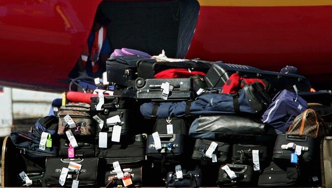 Baggage handlers in the hold, upper left, and hidden at right, load checked luggage aboard a Southwest Airlines jet as a tram carrying more bags passes in the foreground at Los Angeles International Airport on Aug. 11, 2006.