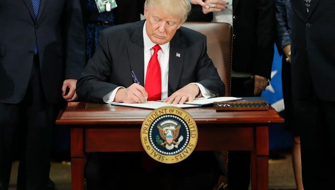 President Donald Trump signs an executive order for border security and immigration enforcement improvements at the Department of Homeland Security in Washington, D.C. on Wednesday.