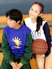 St. Paul Christian Warriors' Chloe Miranda sits with one of the Taiwan Sunshine kids during the Asian Christian School's Conference community service outreach program at the 2017 ACSC Girls Baketball Tournament in Taichung, Taiwan.