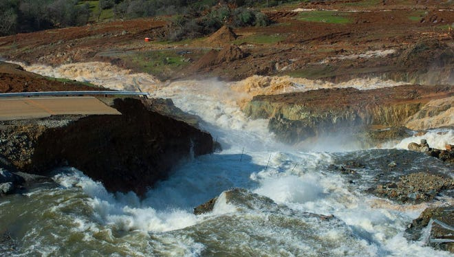 A handout picture provided by the California Department of Water Resources (DWR) shows water from the Oroville Dam Auxiliary Spillway at Lake Oroville eroding the roadway just below the spillway that leads to the spillway boat ramp, in Oroville, Calif.