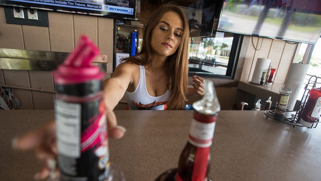 Mariah Materiale, 22, of Cape Coral,  prepares her work area in the outside bar of Hooters Monday afternoon. Materials will be heading to Las Vegas to represent her Hooters in the 21st Annual Hooters International Pageant.