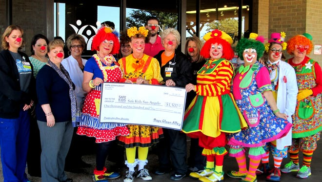 Members of the Oops Clown Alley present a check to Safe Kids San Angelo Nov. 16.