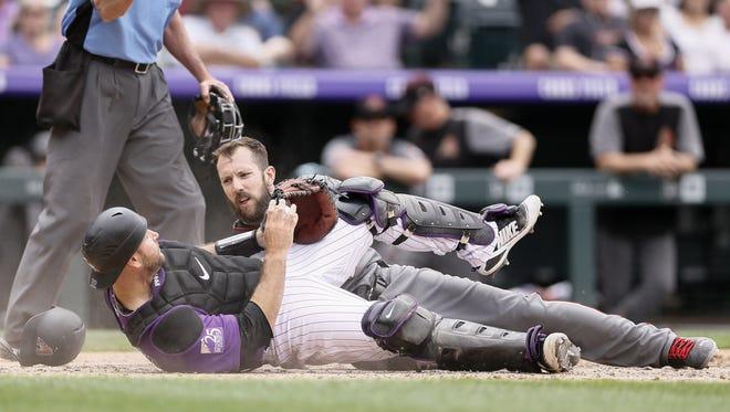 Jul 12, 2018; Denver, CO, USA; Arizona Diamondbacks right fielder Steven Souza Jr. (28) is out at home after a collision with Colorado Rockies catcher Chris Iannetta (22) in the sixth inning at Coors Field.