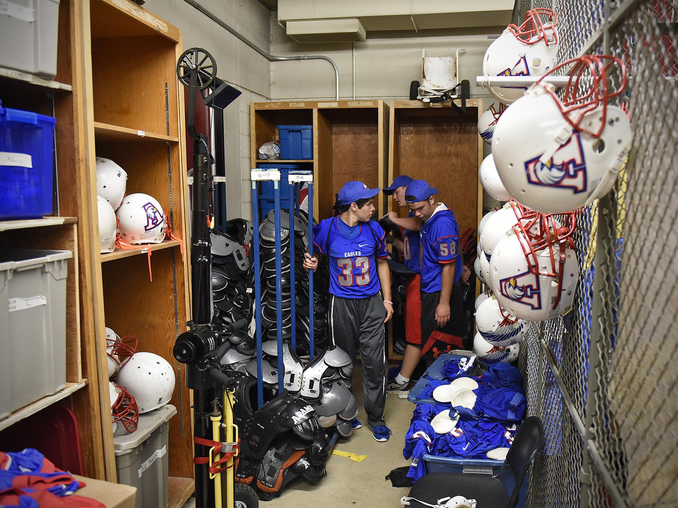 Apollo High School football players sort through equipment Friday on the last day of the school's youth camp. Football practice for all area high schools starts Monday.