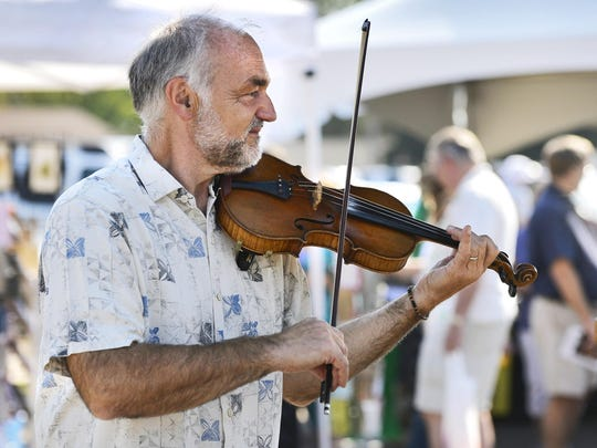 Musician Paul Imholte plays the violin for passers-by during the Millstream Arts Festival. He will be back this year.
