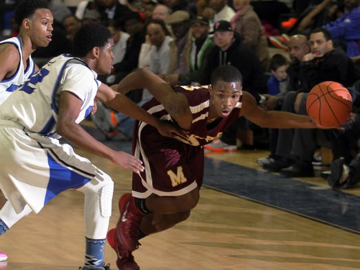 Middletown's Matt Pinkett (left) and Donivan Roy defend against Milford's Tikeace Harris in the first round of the DIAA high school state tournament Wednesday, Feb. 26, 2014 at Middletown High School.