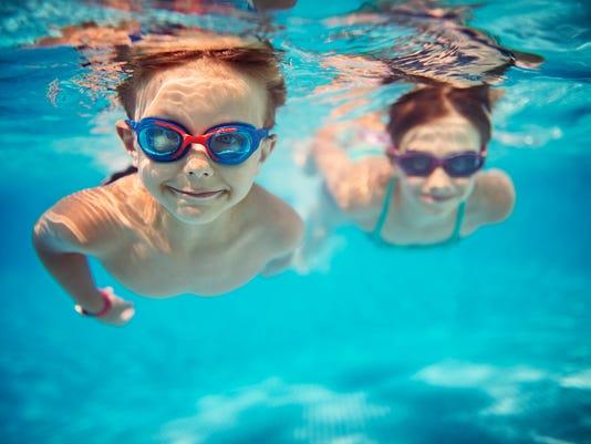 Happy kids swimming underwater in pool