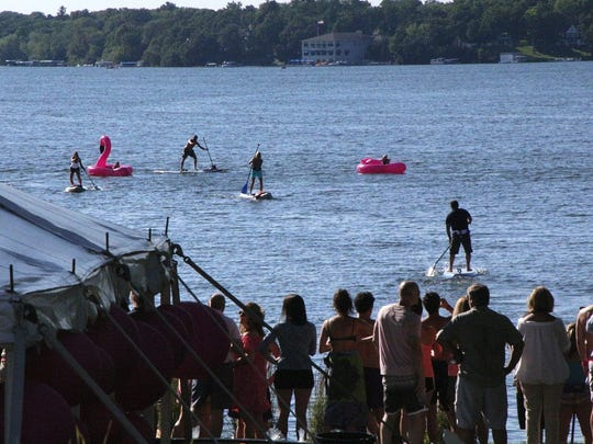 Party-goers race on stand-up paddleboards on Oconomowoc Lake as people watch from the shore.