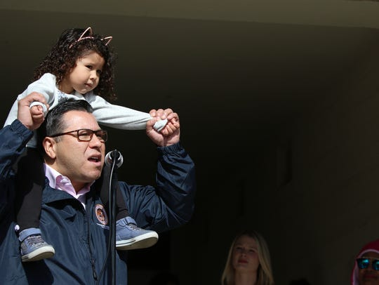 Assemblymen Eduardo Garcia holds his three-year-old daughter, Ella, while speaking at the rally and Palm Springs Women's March held in conjunction with many others nationwide on Saturday, January 20, 2018.