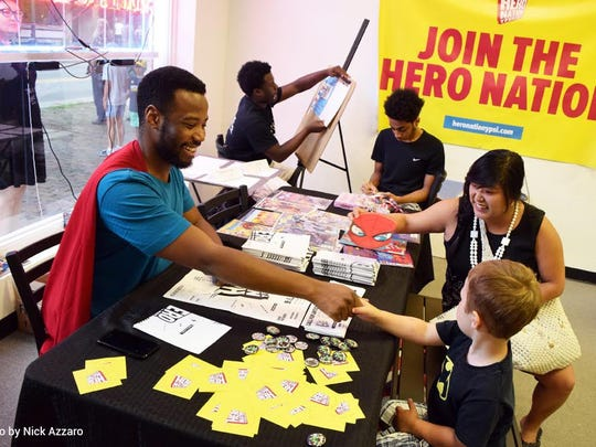 Jermaine Dickerson (left) greets people at a fundraising event for Hero Nation held at Go! Ice Cream in Ypsilanti.