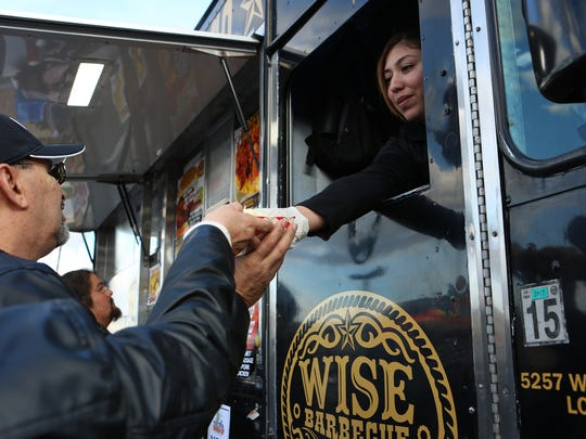 Raquel Martinez of Wise Barbecue hands food to a customer during the Food Truck Mash Up at the Spa Resort Casino in Palm Springs on Saturday, March 17, 2018.