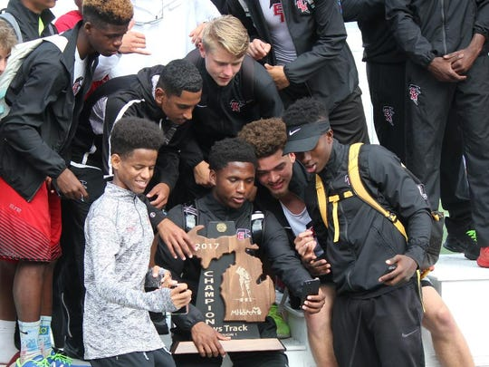 East Kentwood track athletes take selfies with their Division 1 state track and field championship trophy in 2017.