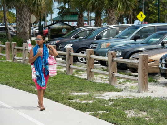"""""""I come here all the time. I would be a little upset if they started to charge for parking at the beach. That would really start adding up for me,"""" said Natalie Booth (left) of Fort Pierce who walks to her car which is parked in a free lot on Sunday, Sept. 18, 2016, at Jetty Park in Fort Pierce. Fort Pierce has addressed a lack of parking by enforcing its 2-hour time limit in downtown for on-street parking and by leasing lots near the beach that allow free, unlimited parking."""