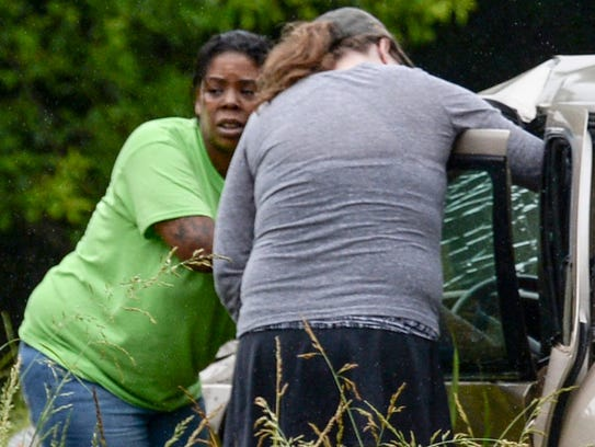 Two women check on an 64-year old woman involved in