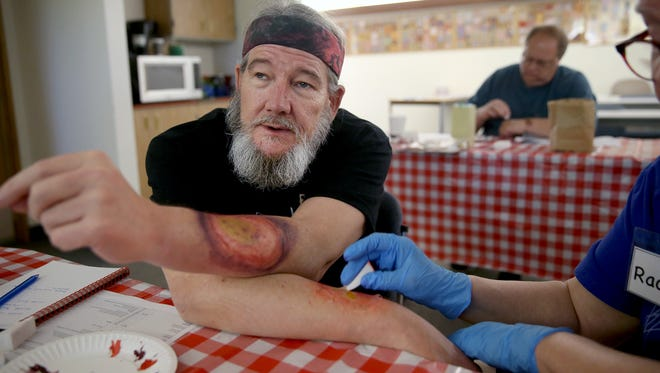 Kevin Ransier from the Kitsap County CERT has a fake disaster makeup painted on his arms by Rachel Yobs from Bainbridge Island at the Moulage Mayhem class on Saturday at the Central Kitsap Fire and Rescue Station 41.