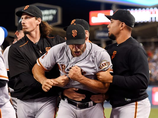 San Francisco Giants starting pitcher Madison Bumgarner, center, yells as he is pulled away by teammates after he and Los Angeles Dodgers' Yasiel Puig got into a scuffle that emptied both benches after Puig was thrown out at first by Bumgarner during the seventh inning of a baseball game, Monday, Sept. 19, 2016, in Los Angeles. (AP Photo/Mark J. Terrill)