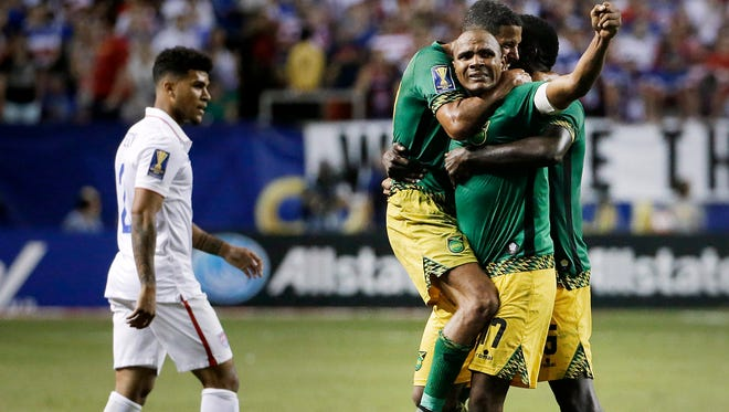 Jamaica's Rudolph Austin, facing camera, celebrates with teammates Joel McAnuff, left, and Je-Vaughn Watson, right, as United States' DeAndre Yedlin walks off the pitch after Jamaica defeated the United States 2-1 in a CONCACAF Gold Cup soccer semifinal Wednesday, July 22, 2015, in Atlanta.