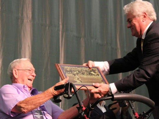 Ove Johnasson presents Wally Bullington, his former coach, with a plaque during a luncheon honoring Johansson and former ACU teammate Wilbert Montgomery on Oct. 22, 2016. The plaque shows Johansson's record 69-yard field goal Oct. 16, 1976. Then the Wildcats coach, Bullington told a reporter the team needed three points, which is noted on the plaque.