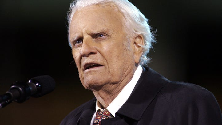 The Rev. Billy Graham speaks to the crowd on a rainy