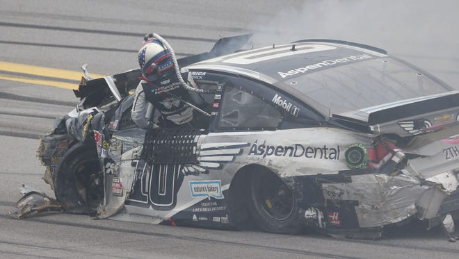Danica Patrick climbs out of her charred and ripped up race car after crashing with Matt Kenseth during the 2016 GEICO 500 at Talladega Superspeedway.