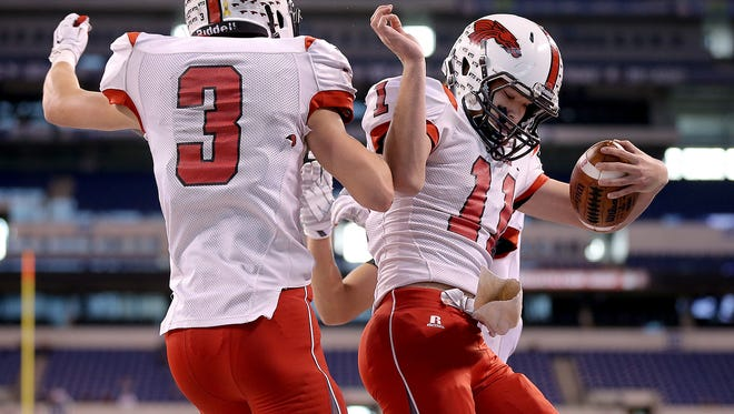New Palestine's QB Alex Neligh,right, celebrates his touchdown run with Garrett Kuhn,left,  in the first half of their game. The New Palestine Dragons took on the New Prairie Cougars in the IHSAA Class 4A State Football Championship game Friday, November 28, 2014, afternoon at Lucas Oil Stadium.