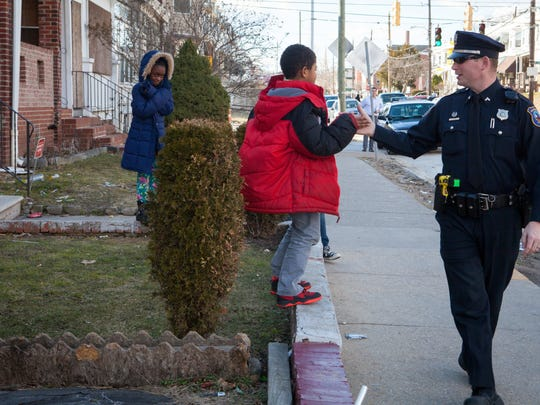 Wilmington police Officer Devon Jones high-fives a boy as he patrols a neighborhood on March 17. Many Delaware police departments are placing a renewed focus and more resources on recruiting.