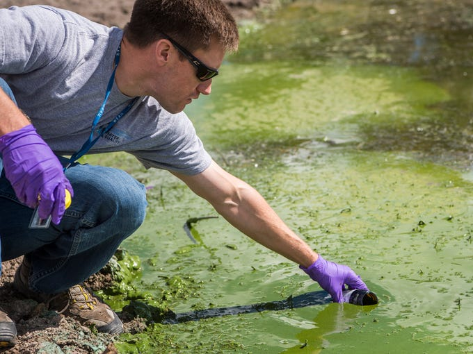 Water quality technician Ryan Parker takes a sample