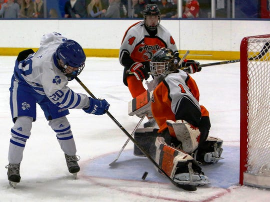 Catholic Central's Mitch Morris (left) tries to stuff the puck past Rice goalie Ryan Hoffman as defenseman Joe Gammicchia (4) looks on.