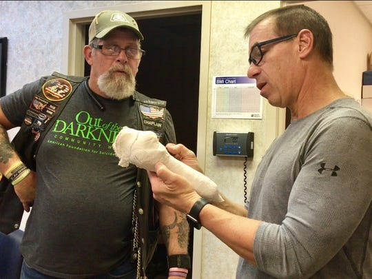 Tom Whitehurst shows Furgus' owner, Bill Lawrence, the cast of the pup's new leg.