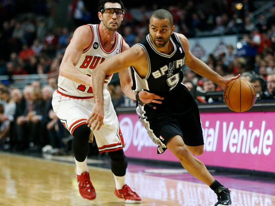 San Antonio Spurs point guard Tony Parker (9) dribbles past Chicago Bulls shooting guard Kirk Hinrich (12) during the first half of an NBA basketball game on Tuesday, March 11, 2014, in Chicago. (AP Photo/Andrew A. Nelles)