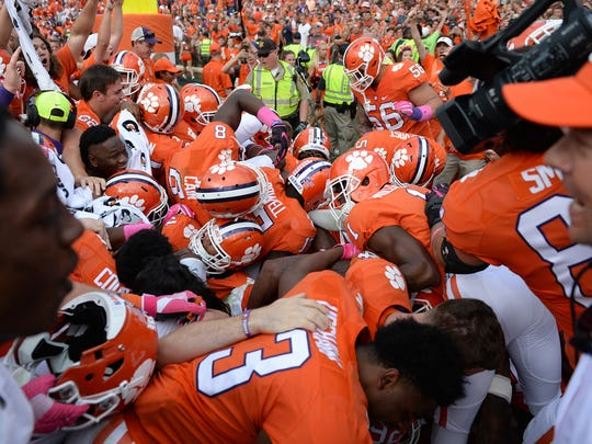 Clemson players dogpile on defensive back Marcus Edmond (29) after he intercepted an N.C. State pass in overtime to secure the Tigers' 24-17 win on Oct. 15 at Clemson's Memorial Stadium.