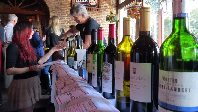 Janet Asher of M&J Wines pours a sample for Marena Bracaloni during the last year's Seville Quarter Wine Festival.   This year, the festival becomes the Seville Quarter Wine & Food Festival.