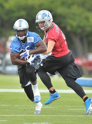 Matthew Stafford hands off to Theo Riddick during training camp last year.