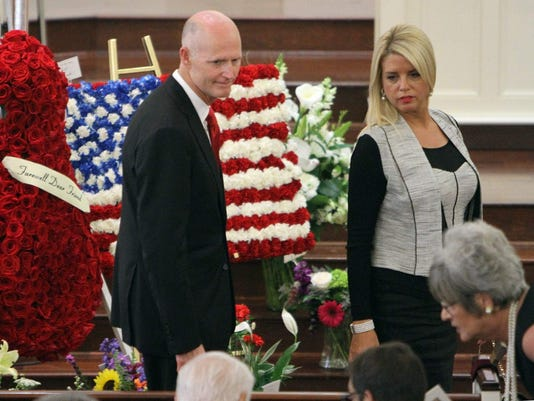Florida Gov. Rich Scott and Attorney General Pam Bondi arrive at a service celebrating the life of Alfred Austin. Scott greeted attendees as they entered the church. ANDY JONES/STAFF
