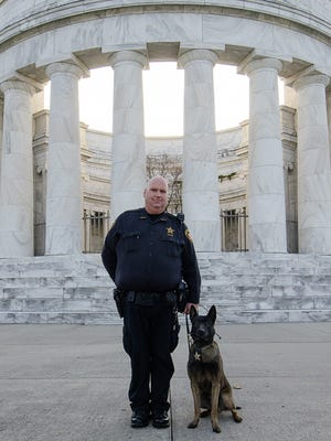 Deputy DJ Barron and Taz stand in front of the Harding Memorial in this file photo. The Marion County Sheriff's Office announced that Taz died earlier this week.