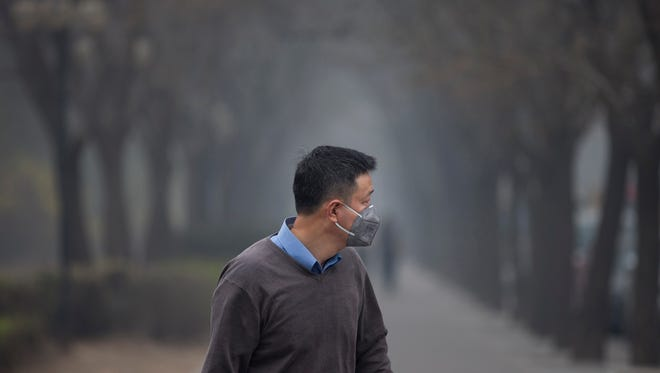 A man wearing a mask walks past trees shrouded with pollution haze in Beijing on March 27.