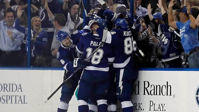 Tampa Bay Lightning center Tyler Johnson (9) is congratulated by teammates after he scored a goal with 1.1 seconds left in the third period of Game 3.