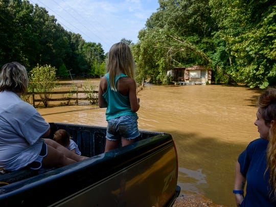 Aubree Northcott, center, 7, looks out over flood waters that rose up the her family member's porches in the morning hours after flash floods swept through low lands and creek beds at Swink Road in Medon, Tenn., Monday, July 16, 2018.